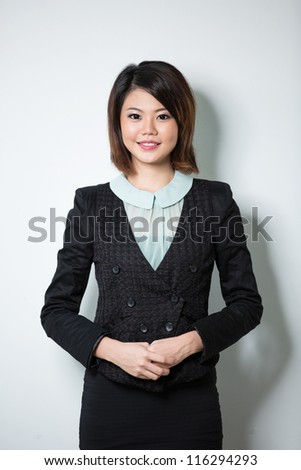 Attractive Asian Business Woman leaning against a white wall. - stock photo