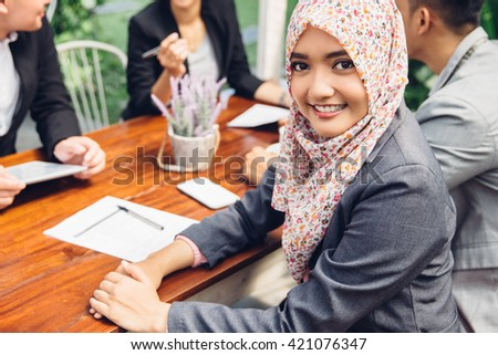 Attractive asian businesswoman smiling at the camera during a business meeting - stock photo