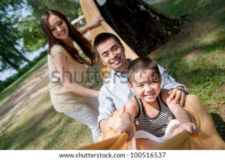 Attractive asian family on a hammock - stock photo