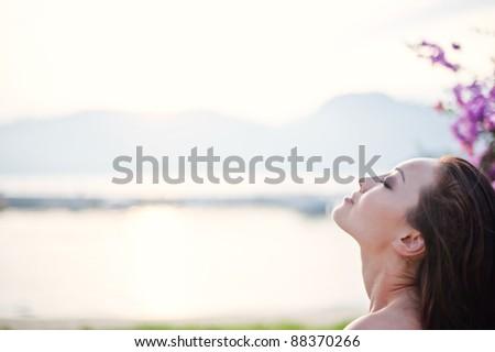 Attractive Asian Female enjoying the sea breeze - stock photo