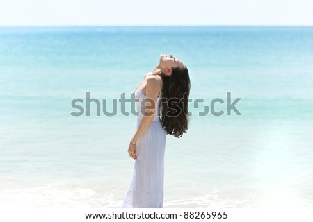 Attractive asian female relaxing on the beach appreciating the sun - stock photo