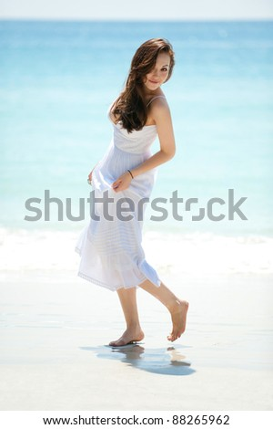 Attractive asian female walking on the beach looking back - stock photo