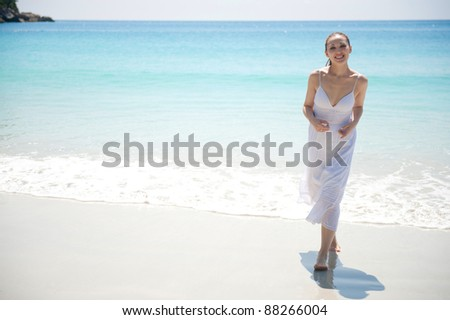 Attractive asian female walking on the beach towards the camera - stock photo