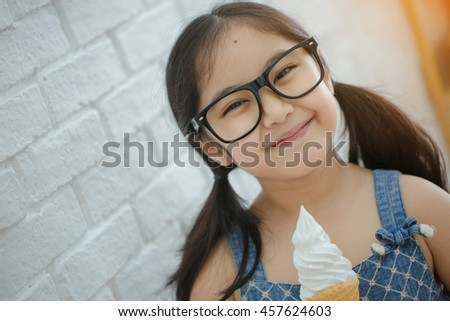 Attractive Asian girl enjoy eating soft ice-cream - stock photo
