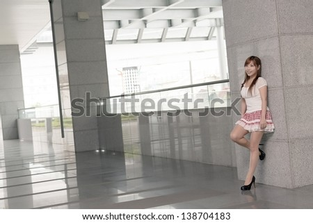 Attractive Asian girl, full length portrait in modern city. - stock photo