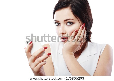 Attractive asian girl in her twenties worried hold cell phone isolated on a plein background shot in a studio  - stock photo
