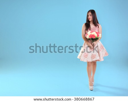 Attractive Asian girl standing with roses bouquet and looking at copy space on her side, full body shot over blue background - stock photo
