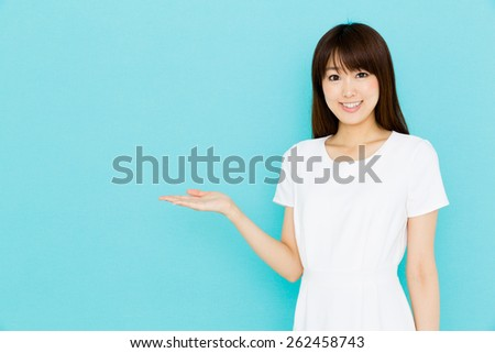 attractive asian nurse showing on blue background - stock photo