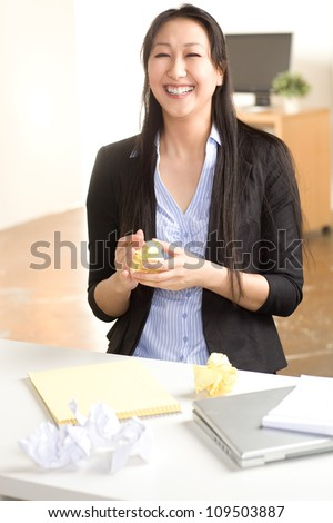 Attractive Asian woman at work in office setting with straight black hair wearing black suit and blue shirt - stock photo