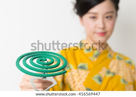 attractive asian woman in a yukata having mosquito-repellent incense - stock photo