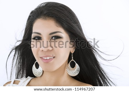 Attractive Asian woman in stylish earrings with her long dark hair blowing in the breeze - stock photo