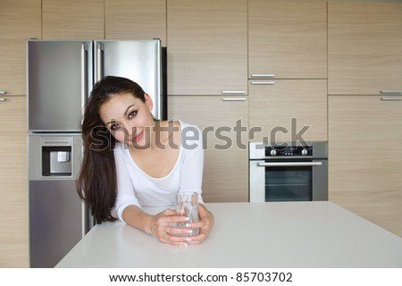 Attractive Asian Woman in the kitchen drinking water - stock photo