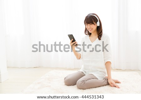 attractive asian woman listening music - stock photo