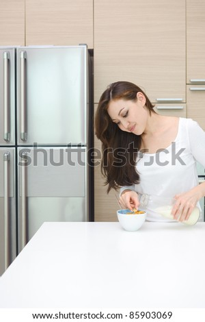 Attractive Asian Woman preparing breakfast having cereals with milk - stock photo