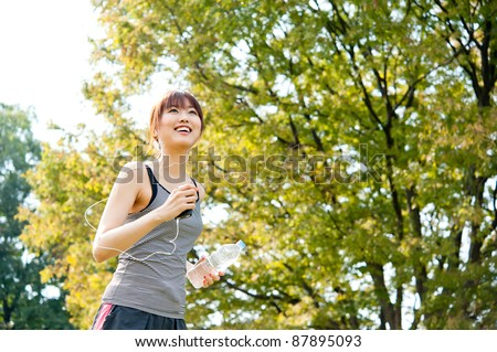 attractive asian woman running in the park - stock photo