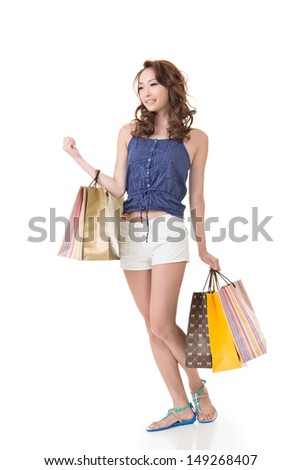Attractive Asian woman shopping and holding bags, full length portrait isolated on white background. - stock photo