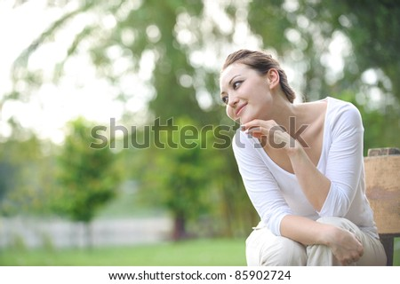 Attractive Asian Woman sitting on a bench in the park - stock photo
