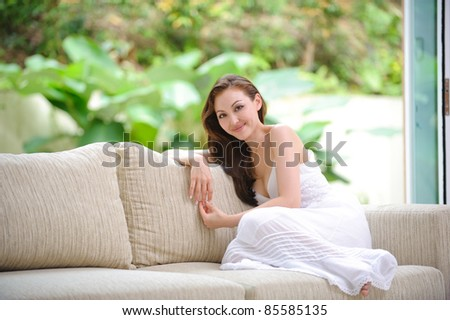 Attractive Asian woman sitting on a sofa in the living room - stock photo