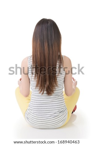 Attractive asian woman sitting on the ground. Rear view. Full length portrait with copyspace of white wall. - stock photo