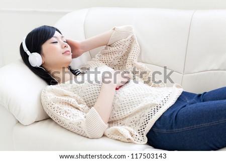 attractive asian woman sleeping on the sofa - stock photo