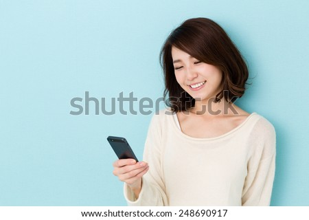 attractive asian woman using smart phone isolated on blue background - stock photo