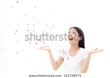 attractive asian woman with falling petals on white background - stock photo