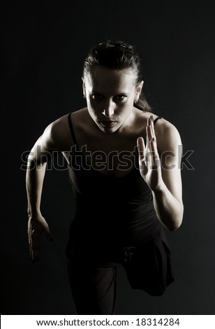attractive athlete running over black background - stock photo
