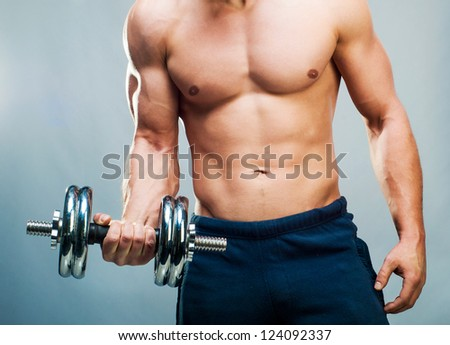 attractive athletic male torso with dumbbells - stock photo
