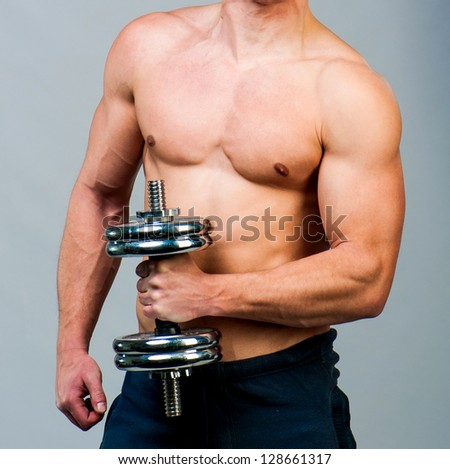 attractive athletic male torso with dumbbells in hand - stock photo