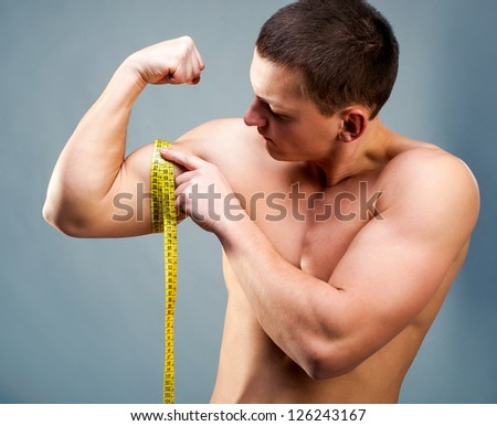 attractive athletic man measuring his biceps - stock photo
