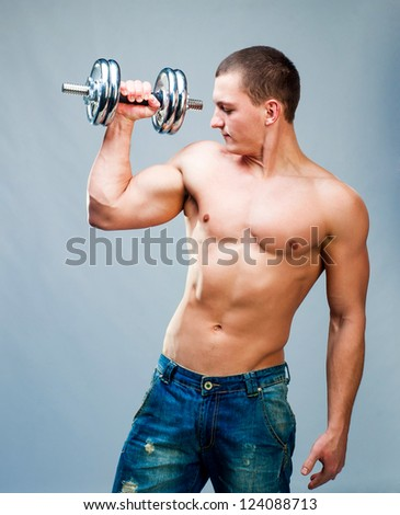 attractive athletic man with dumbbells in hand - stock photo