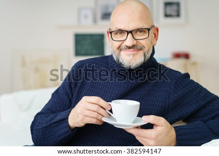 Attractive bald middle-aged man relaxing on the sofa at home enjoying a cup of coffee or tea and smiling at the camera - stock photo