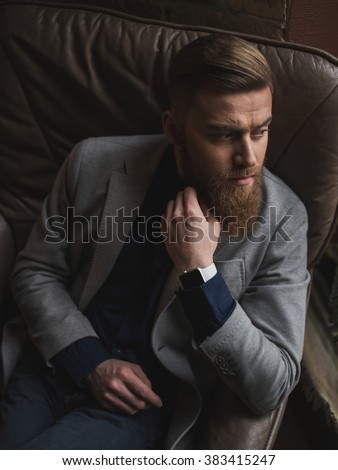 Attractive bearded businessman is deciding serious question - stock photo