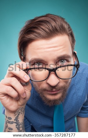 Attractive bearded hipster is examining and looking at camera with interest. He is standing and touching eyeglasses with aspirations. Isolated - stock photo