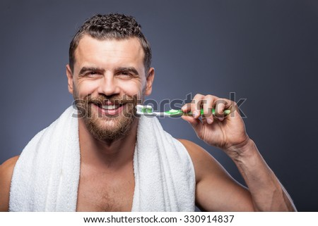 Attractive bearded man is brushing his teeth. He is standing and holding tooth-brush with tooth-paste on it. The man is carrying white towel and smiling. Isolated on grey background - stock photo