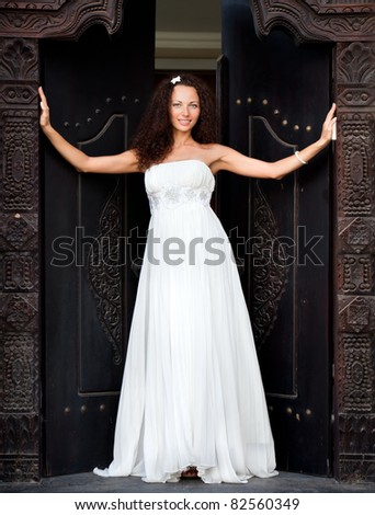 Attractive beautiful bride is leaning on the door vintage - stock photo