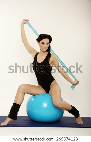 Attractive beautiful young adult pretty brunette sporty woman in black dress with blue fitness ball isolated on white background - stock photo