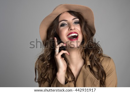 Attractive beauty wearing hat and autumn clothes laughing while talking on the mobile phone over gray studio background - stock photo