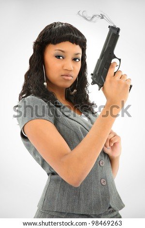 Attractive Black Female Holding Smoking Handgun While Looking At The Camera - stock photo
