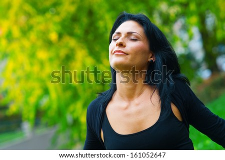 attractive black hair woman breathing and relaxing in nature - stock photo