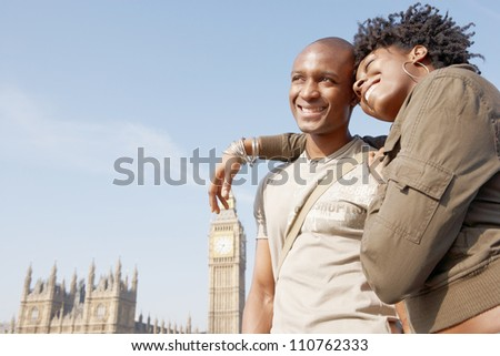 Attractive black tourist couple standing by Big Ben while visiting London city on vacation, smiling. - stock photo