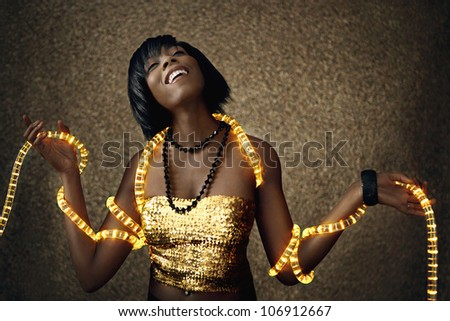 Attractive black woman dancing with Christmas lights around her body, smiling. - stock photo