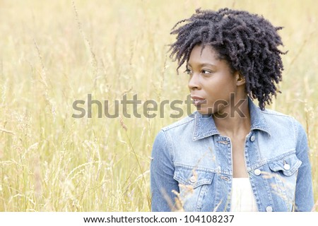 Attractive black woman standing in a long grass field. - stock photo