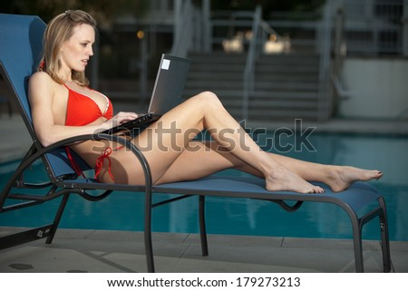 Attractive blond caucasian woman working by poolside - stock photo