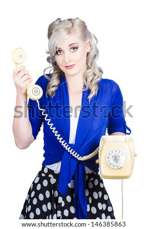 Attractive blond female secretary handing over the receiver on vintage yellow phone, its for you - stock photo