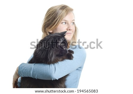Attractive blond girl holding black tomcat looking right, copy space - stock photo