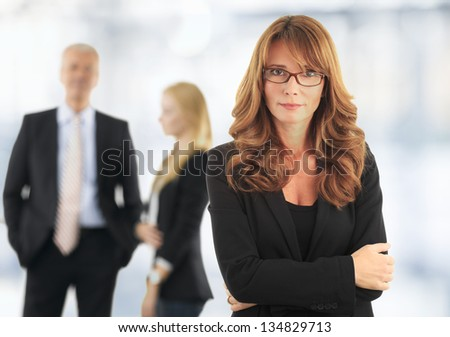Attractive blond mature business woman with her colleagues in the background - stock photo