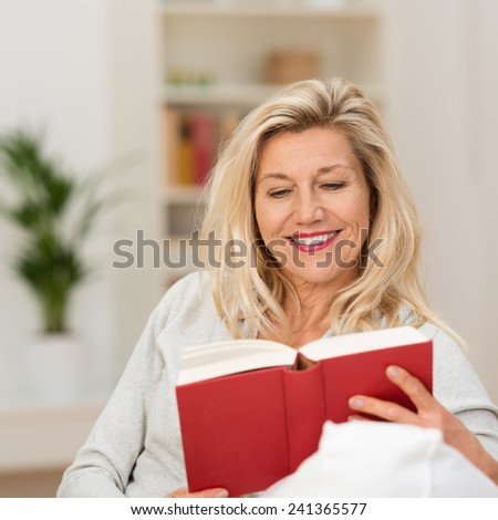 Attractive blond middle-aged woman enjoying reading a book sitting on the sofa in her living room smiling as she reads - stock photo