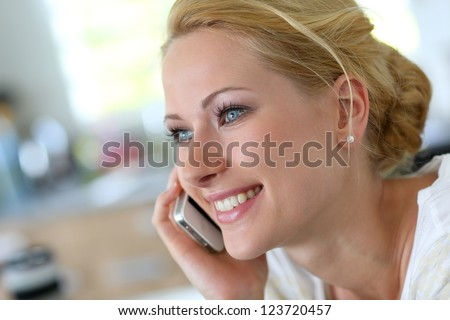 Attractive blond woman at home talking on mobilephone - stock photo