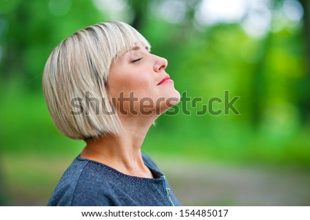 attractive blond woman breathing and relaxing in nature - stock photo